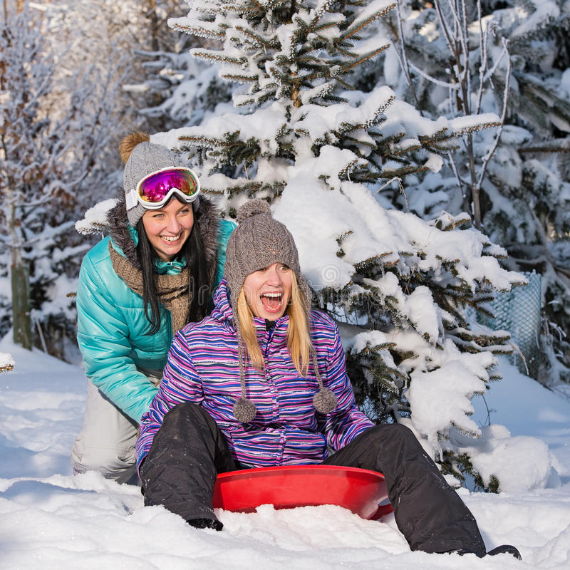 Two female friends on bobsleigh winter snow royalty free stock photos