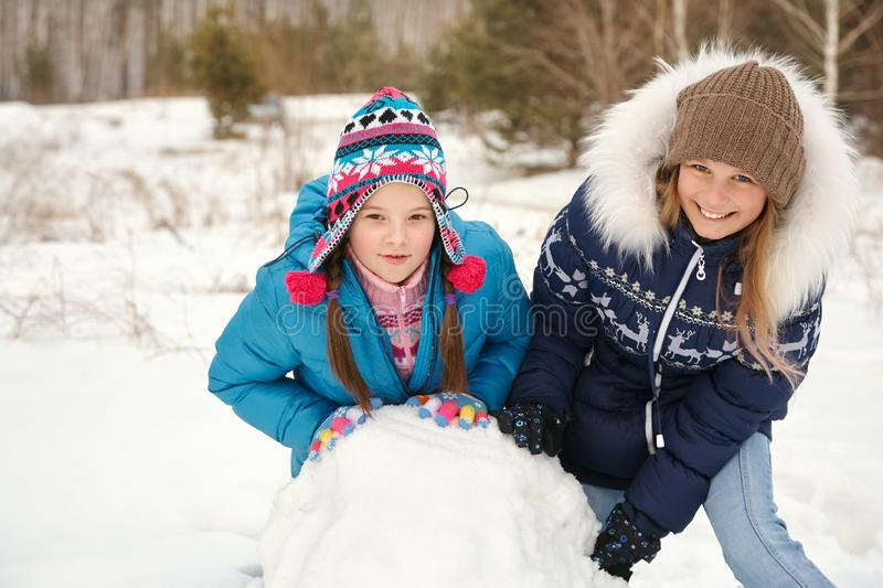 Twofunny girls building a snowman in the winter. Two female friends building a snowman. funny girls on a walk in the winter outdoors stock photos