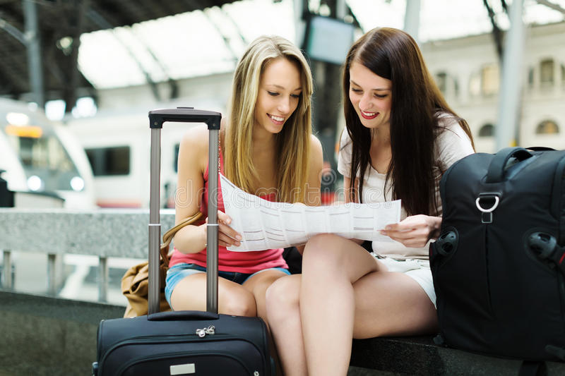 Two female friends with city map stock images