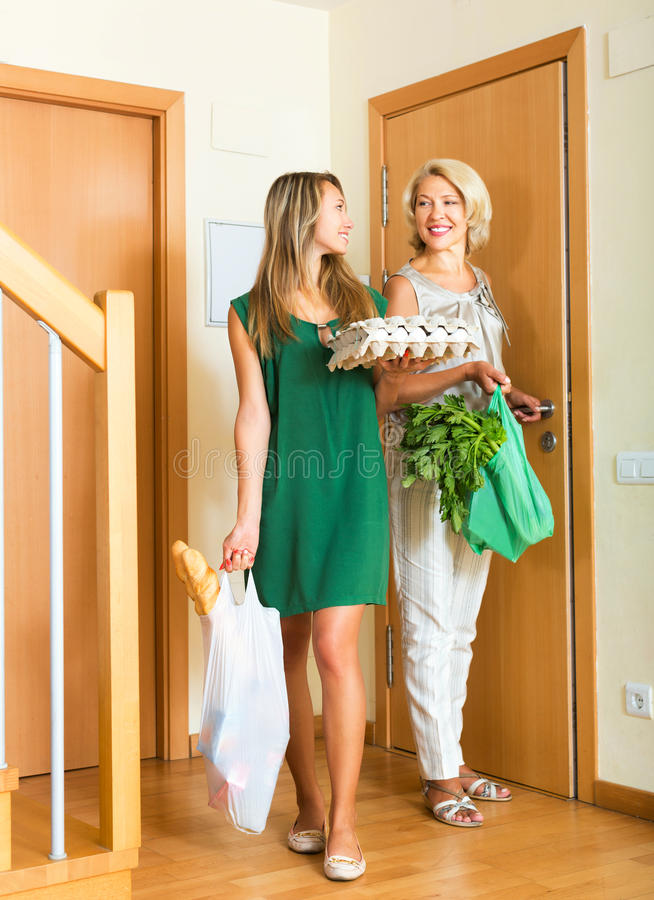 Two female friends coming home. With bags after foodstuff shopping stock image