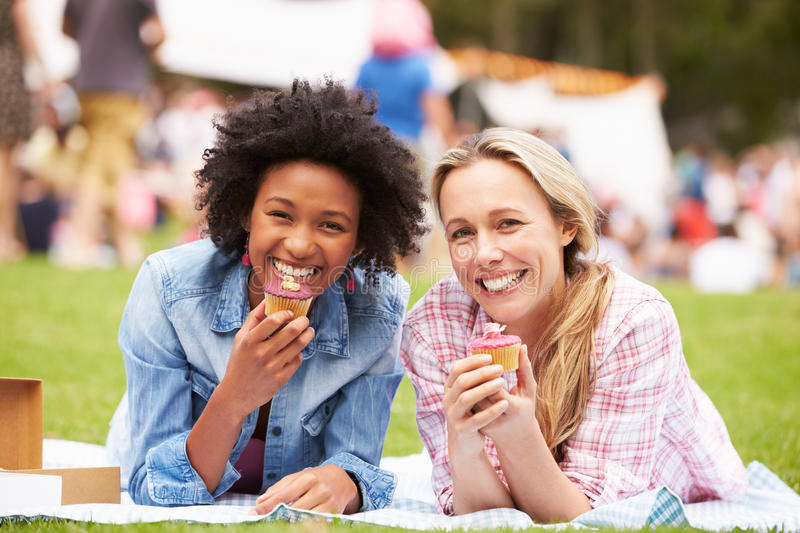 Two Female Friends Enjoying Cupcakes At Outdoor Summer Event stock photos