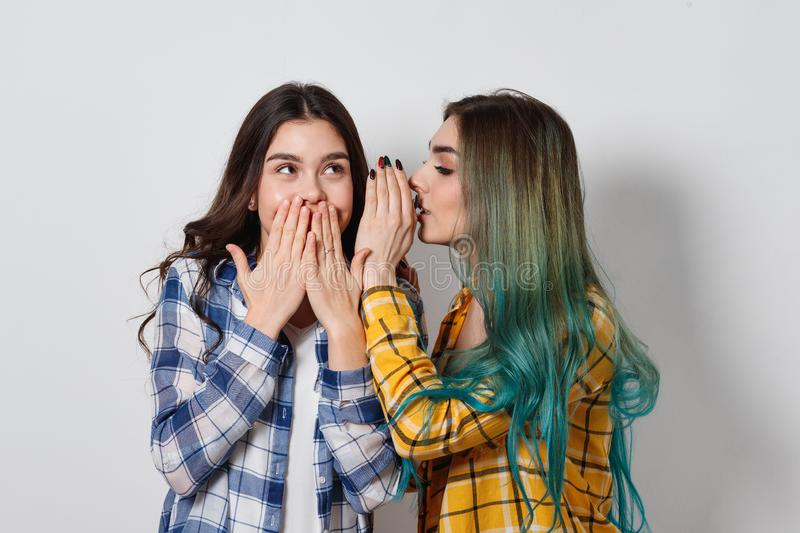 Two female friends gossiping. One girl tells the secrets of the other in ear stock photography