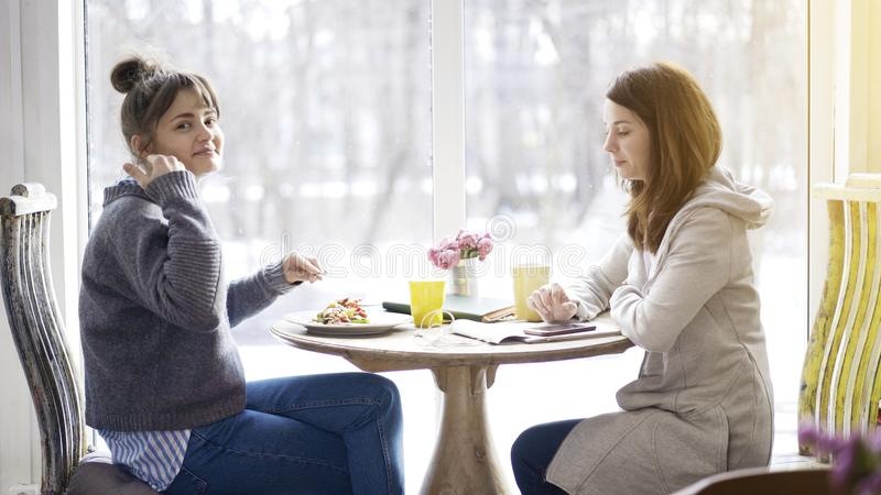Two female friends happy meeting in a cafe royalty free stock photos
