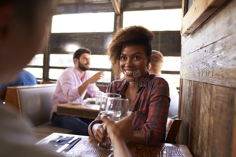Two female friends making a toast at a table in a bar stock photography