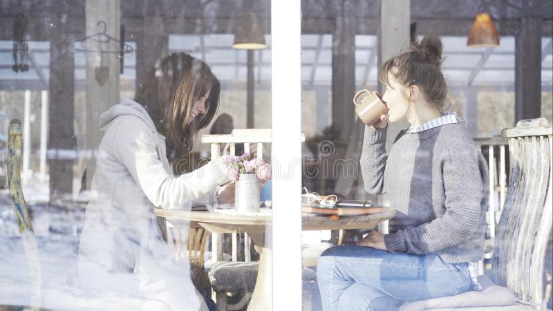 Two female friends meeting in a cafe to talk stock images