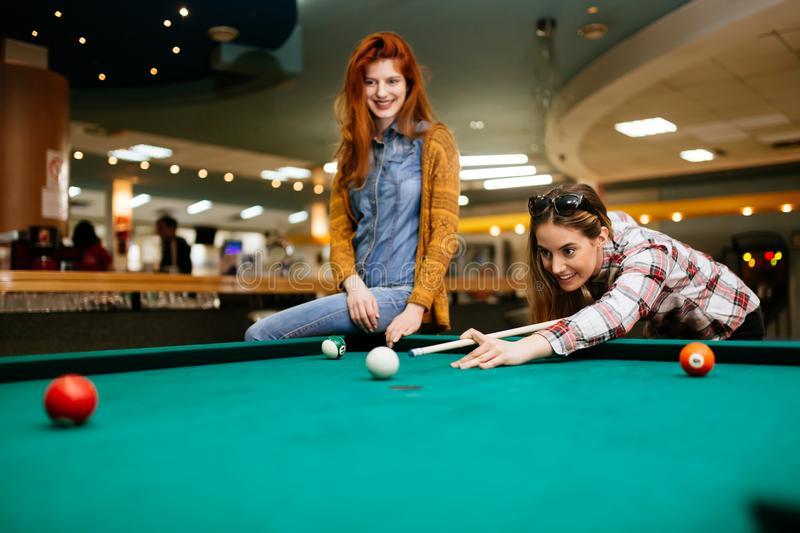 Two female friends playing snooker royalty free stock photos