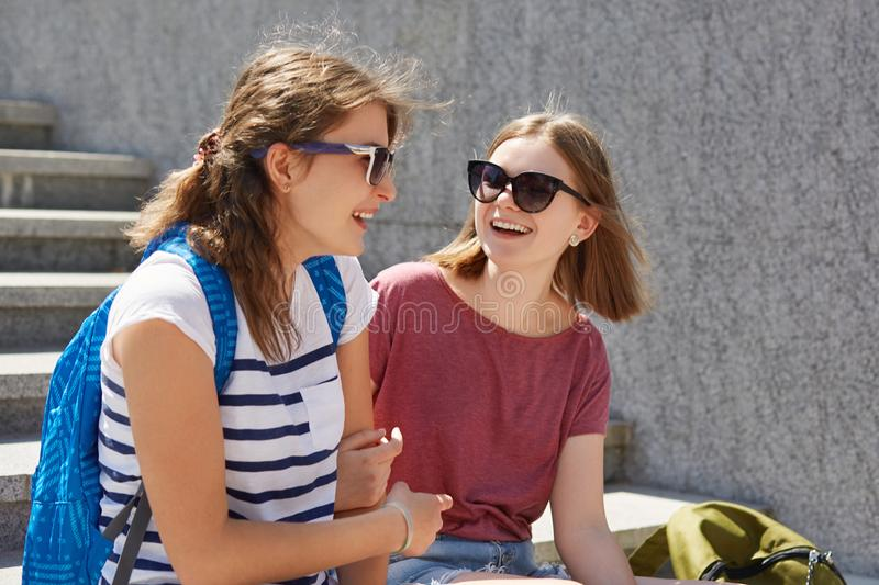 Two female friends sit on steps outdoor, have lively communication, wears sunglasses, casual t shirt, carry rucksacks, have positi royalty free stock images