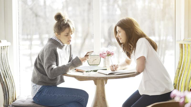 Two female friends students sitting in a cafe face to face royalty free stock image