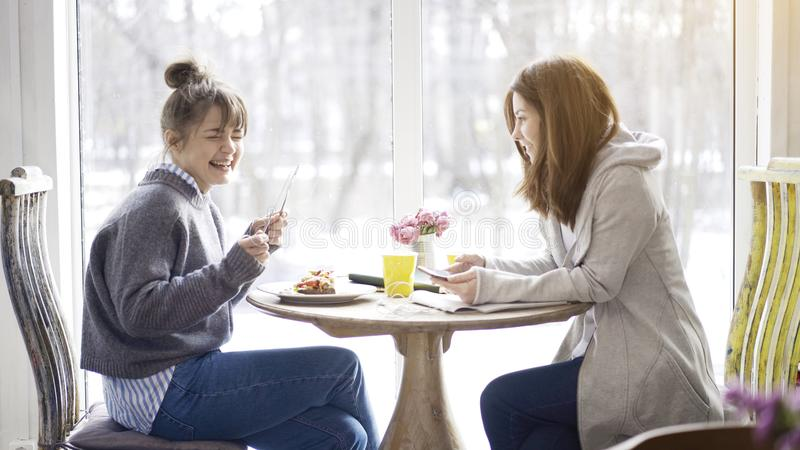 Two female friends talking laughing in a cafe royalty free stock images