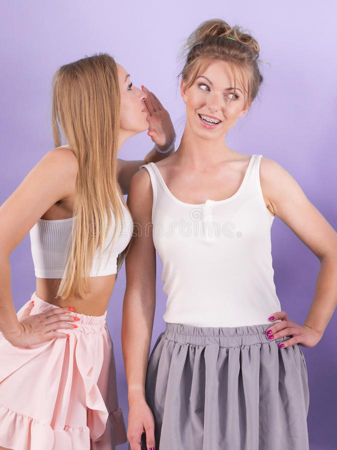 Two females gossiping having fun. Two female friends telling tales gossiping about somebody having fun. Social human relations concept royalty free stock photo