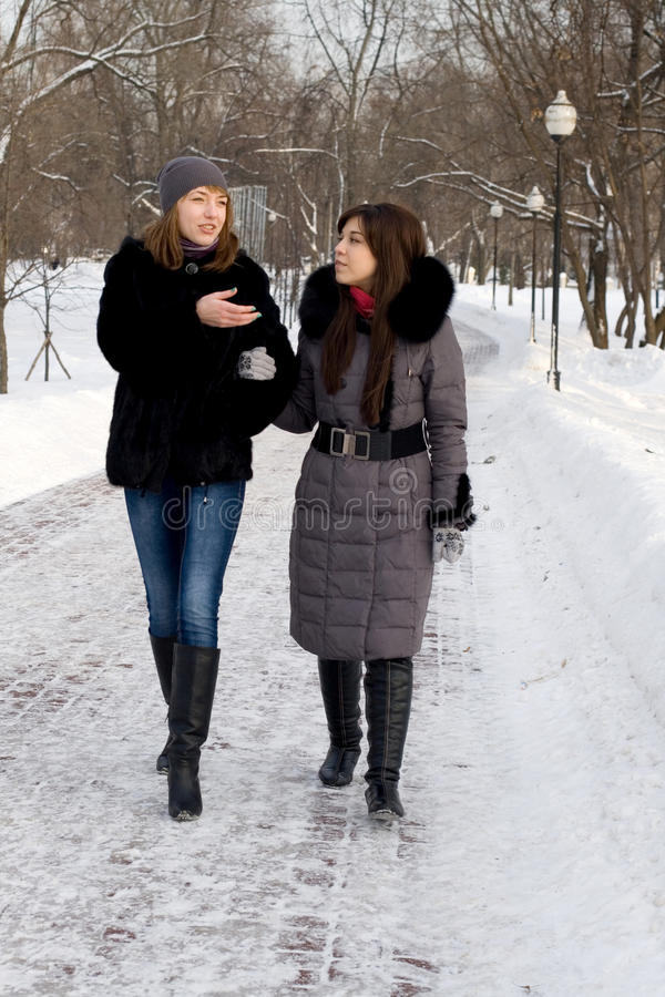 Two female friends walking in park stock photos