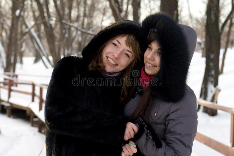 Two female friends walking in park stock images
