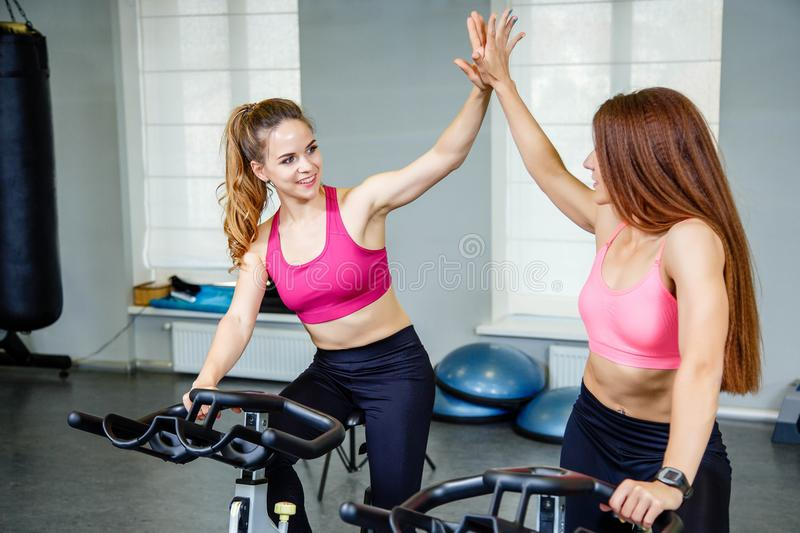 Two female friends wearing sportswear giving high five while cardio workout in gym. royalty free stock images