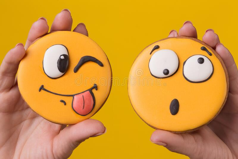 Two female hands are holding two gingerbread cookies in the form of funny emoticons with different emotions, concept. On yellow background stock image