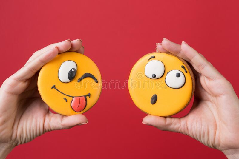 Two female hands holding two gingerbread cookies in the form of funny emoticons with emotions, concept, on red background. Copy space royalty free stock photo