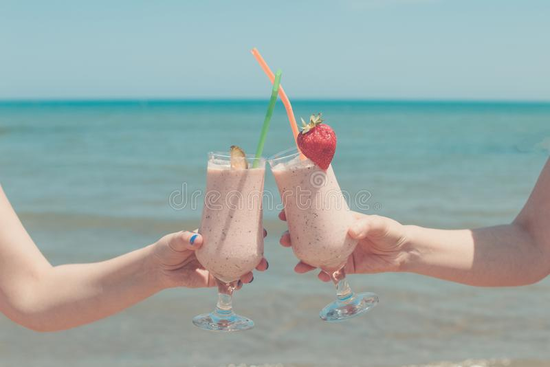 Two female hands are holding strawberry milkshakes on the background of the sea stock image