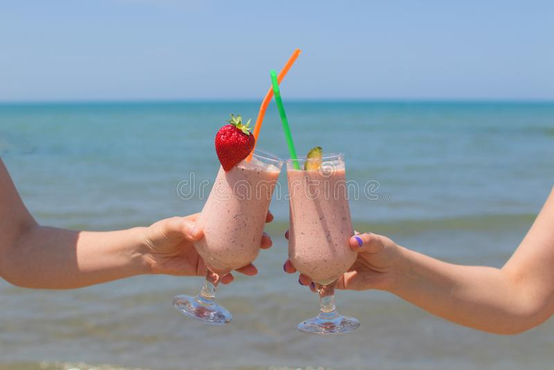 Two female hands are holding strawberry milkshakes on the background of the sea stock images