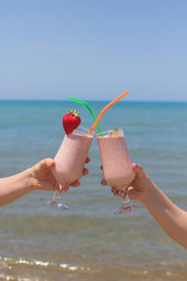 Two female hands are holding strawberry milkshakes on the background of the sea royalty free stock photo