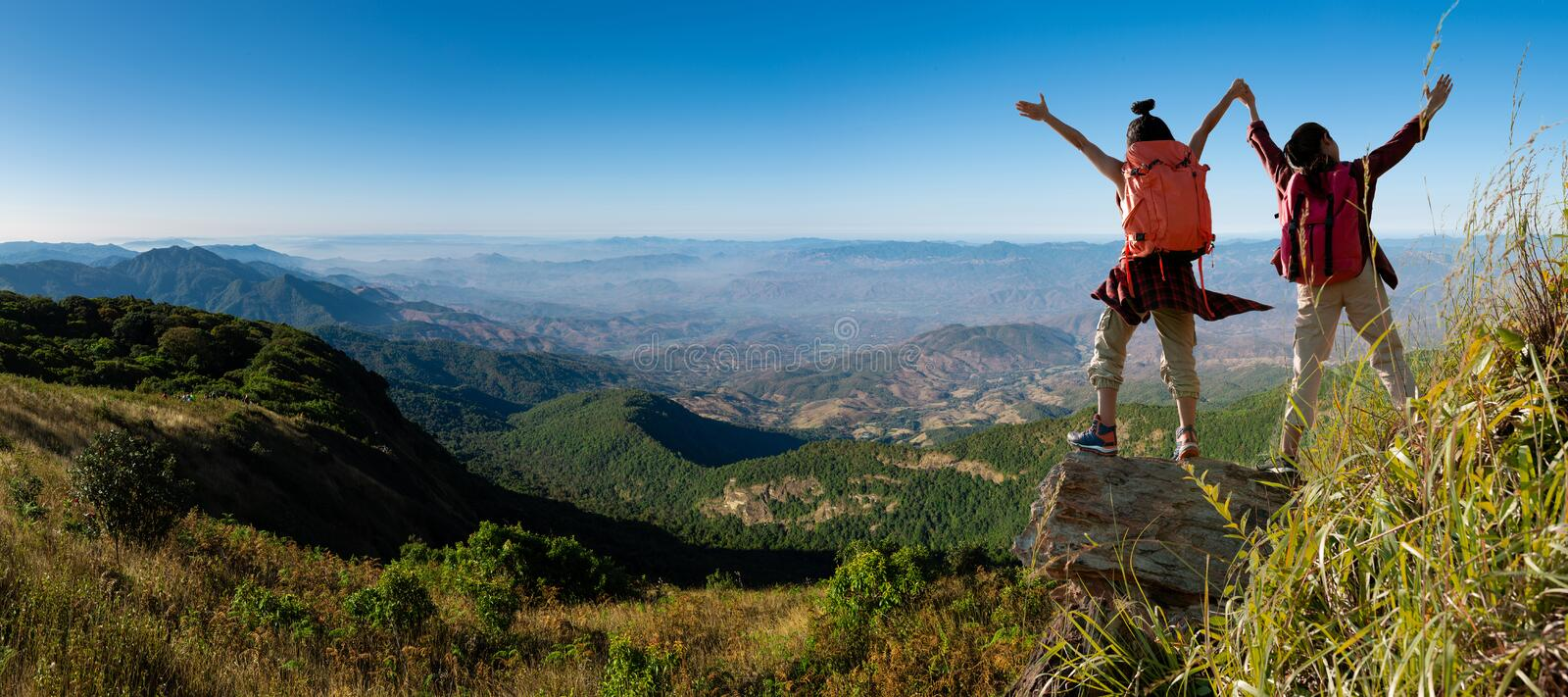 Two female hikers climbing up mountain cliff. Panorama , two female hikers climbing up mountain cliff royalty free stock image