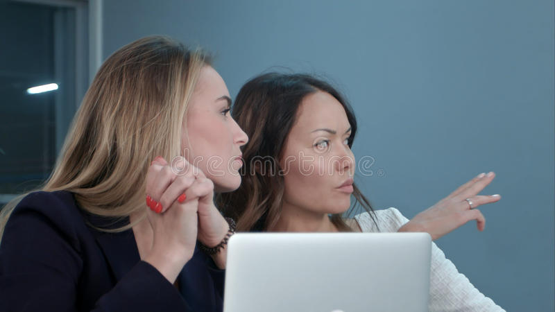 Two female managing directors discussing ideas of project while sitting on conference in office hall royalty free stock photos