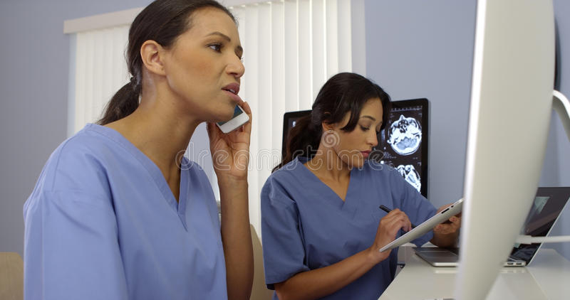 Two female medical personnel working as a team using modern technology royalty free stock photo