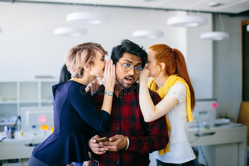Two female office workes wispering important news to Indian chief stock image