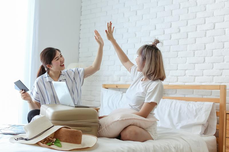 Two female are preparing to travel. Woman going to summer vacation. Two women friends booking tour online holding smart phone and royalty free stock images
