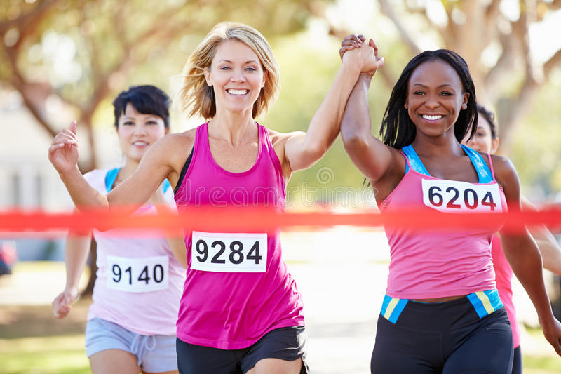 Two Female Runners Finishing Race Together. Two Female Runners HOldong Hands Finishing Race Together stock images