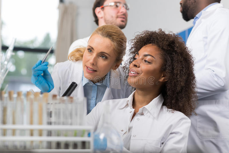 Two Female Scientist Examine Sample Working In Modern Laboratory, Group Of Researchers Making Experiment. In Lab stock photo