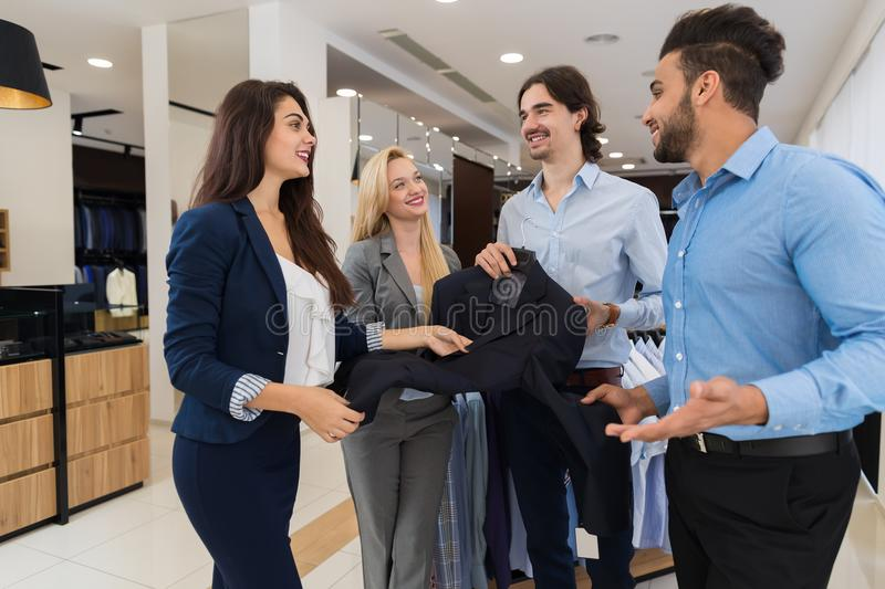 Two Female Shop Assistants Offering Young Businessmen New Suit Helping With Shopping In Luxury Menswear Store stock photography