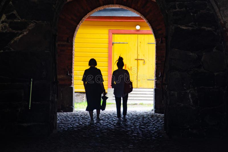 Two female silhouettes in a brick arch with a view of a yellow wooden building stock image