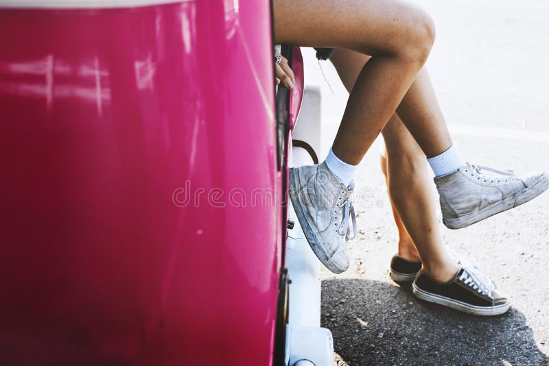 Two Female Sitting on Pink Car stock photos