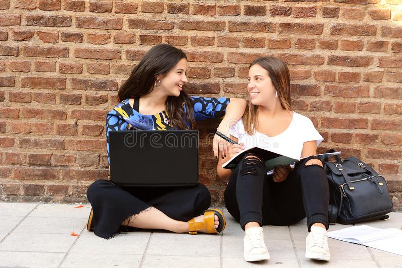 Two female students are preparing for exams. With workbook and laptop computer in urban background. Education concept stock images