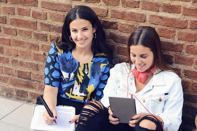 Two female students are preparing for exams. With workbook and tablet PC in urban background. Education concept stock image