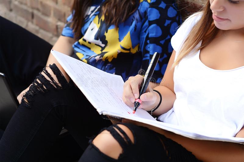 Two female students are preparing for exams. With workbook in urban background. Education concept stock image