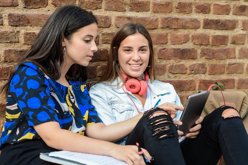 Two female students are preparing for exams. With workbook and tablet PC in urban background. Education concept stock photography