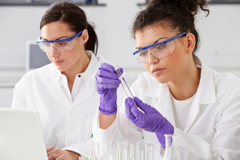 Two Female Technicians Working In Laboratory. Wearing Glasses stock photography