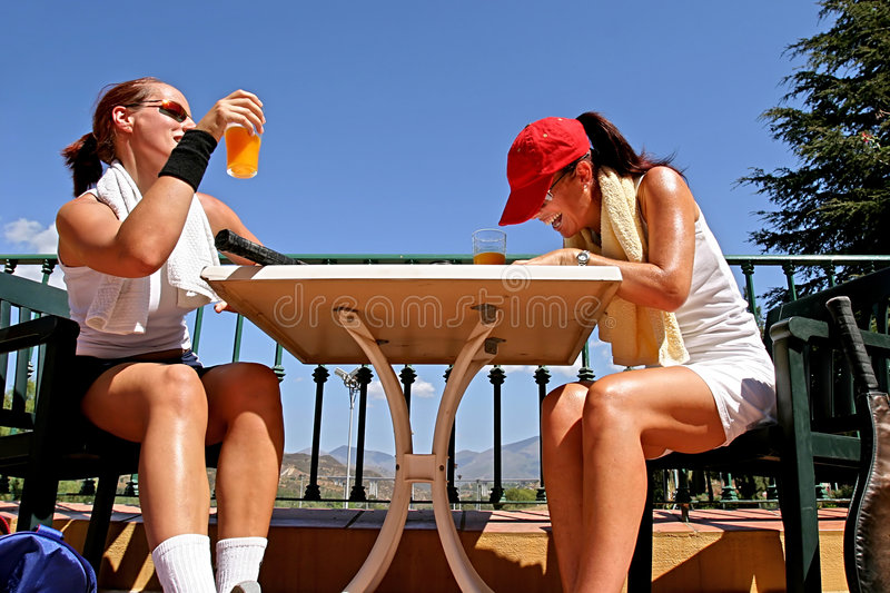 Two female tennis players sharing a joke after a game. Enjoying a glass of orange juice in the sun. royalty free stock photos