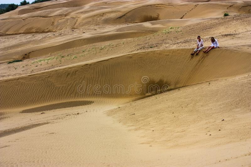Jaisalmer, India - August 20, 2009: two female tourists sitting in the desert in jaisalmer, rajasthan, india royalty free stock image