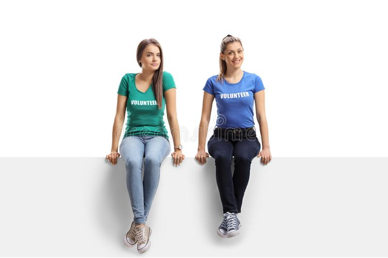 Two female volunteers sitting on a white panel royalty free stock images
