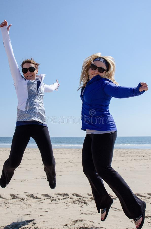 Two female woman friends jump on the beach on a sunny day. Concept for success, achievement royalty free stock image