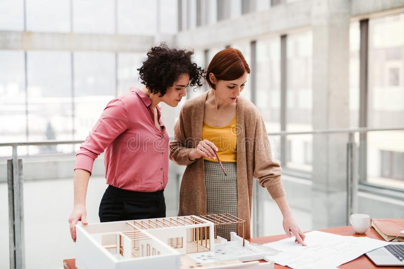 Female young architects with model of a house standing in office, talking. royalty free stock photos