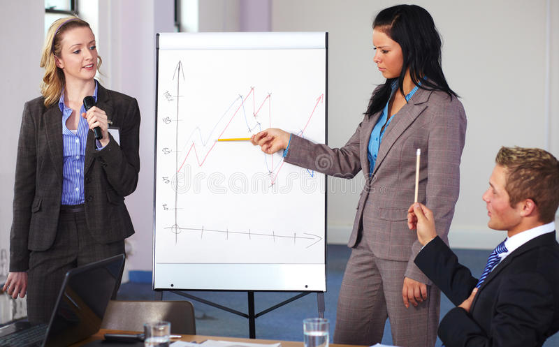 Two females present graph on flipchart. Two females standing and present graph on flipchart during business meeting, have an argue with male sitting at royalty free stock photography
