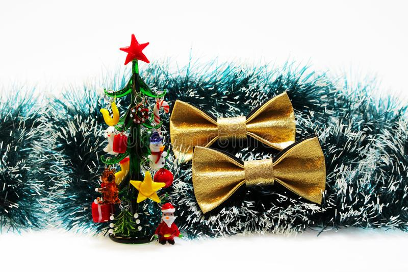 Two festive gold butterfly bow tie against a background of green Christmas tree tinsel and a miniature remembrance glass stock photo