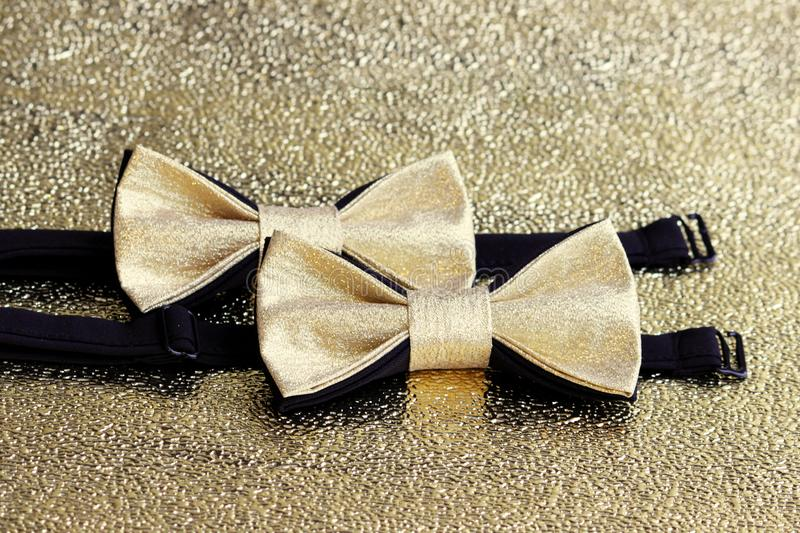 Two festive golden with a black bow tie on a gold background. royalty free stock photography