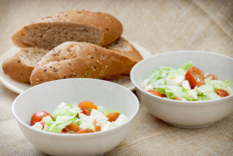 Two fetta salad portions and slices of bread royalty free stock photography