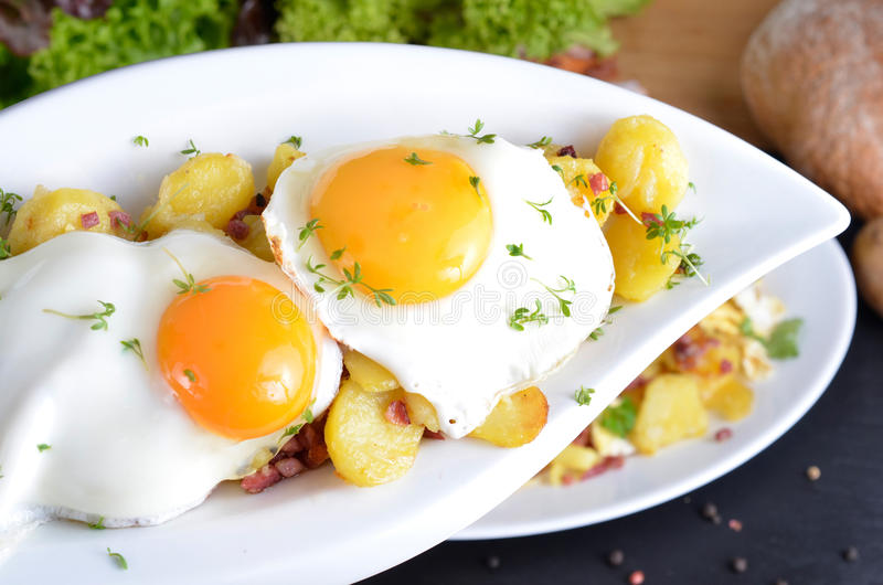Two fied eggs with fried potatoes. Farmer's breakfast, fried eggs with fried potatoes, onions and bacon royalty free stock photography