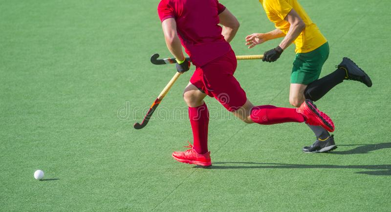 Two field hockey player, fighting for the ball on the midfield during an intense match on artificial grass.  stock photos