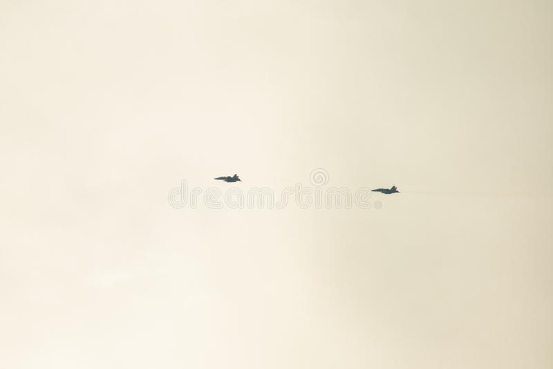 Two fighters flying in formation with a cloudy blue sky in the background stock images