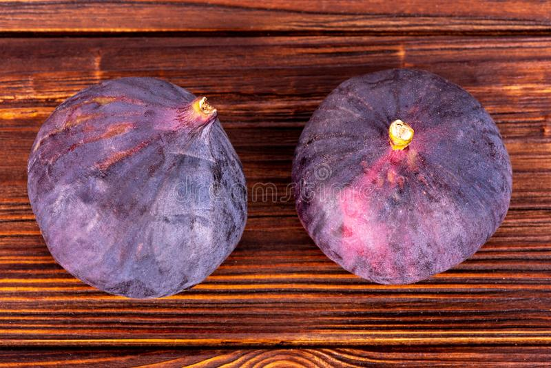 Two figs on wooden surface top view royalty free stock images